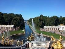 Os conjuntos os maiores da fonte, cascata grande, palácio grande em Petergof, St Petersburg, Rússia C?u azul do ver?o Vista do ab fotografia de stock