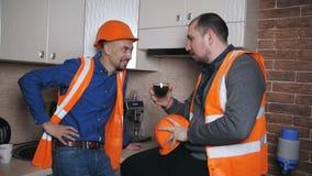 Os construtores atrativos estão bebendo o café em uma ruptura Estão falando e estão sorrindo filme
