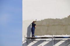 Os construtores dos estucadores emplastraram a parede em uma construção comercial Wor foto de stock royalty free