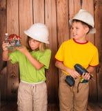 Os construtores pequenos no capacete com uma casa modelam Conce da casa da família Fotos de Stock Royalty Free