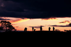 Os contornos de um grupo de pessoas no por do sol no campo aberto Fotos de Stock