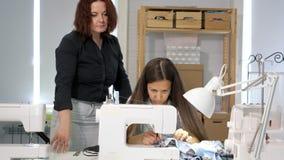 Os controles do professor da costureira olham como o estudante costura na máquina de costura na oficina video estoque