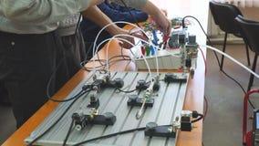 Os coordenadores conectam o painel de controle dos fios com o banco pequeno do teste para experiências video estoque
