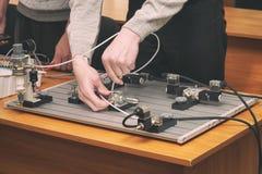 Os coordenadores conectam o painel de controle dos fios com o banco pequeno do teste para experi?ncias fotografia de stock
