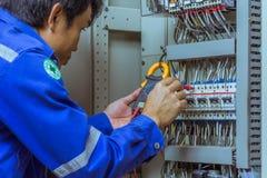 Os coordenadores masculinos estão verificando o sistema elétrico com as ferramentas eletrônicas, braçadeira-em, o grampo ampère,  fotografia de stock royalty free