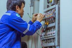Os coordenadores masculinos estão verificando o sistema elétrico com o electroni imagens de stock
