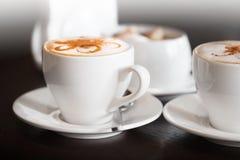 Os copos brancos do cappuccino estão na tabela escura Foto de Stock Royalty Free