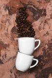 Os copos brancos para o café encheram-se com os feijões de café Vista superior Imagem de Stock