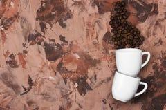 Os copos brancos para o café encheram-se com os feijões de café Vista superior, cópia Imagem de Stock Royalty Free