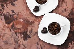 Os copos brancos para o café encheram-se com os feijões e o chocolate de café mim Imagens de Stock