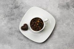 Os copos brancos para o café encheram-se com os feijões e o chocolate de café mim Foto de Stock Royalty Free