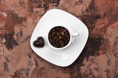 Os copos brancos para o café encheram-se com os feijões e o chocolate de café mim Fotos de Stock