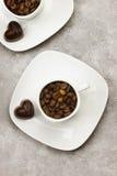 Os copos brancos para o café encheram-se com os feijões e o chocolate de café mim Fotografia de Stock