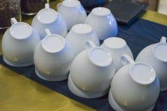Os copos de café branco empilharam de cabeça para baixo após ter lavado os pratos fotografia de stock royalty free