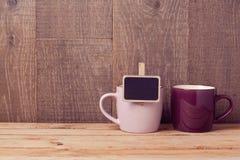Os copos de café na tabela de madeira com quadro assinam Fotos de Stock Royalty Free