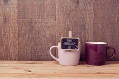 Os copos de café na tabela de madeira com quadro assinam Celebração do dia da amizade Foto de Stock