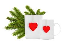 Os copos de chá brancos com etiqueta vermelha e ramo de árvore verde do Natal são Foto de Stock Royalty Free