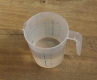 Os copos de medição um litro molham no fundo de madeira Foto de Stock Royalty Free