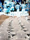 Os copos do café e de café do futebol arranjaram na linha do fundo do futebol Fotografia de Stock Royalty Free