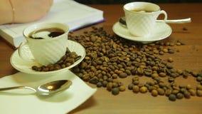 Os copos do café forte, de uma dispersão de feijões de café na tabela e de uma mulher escrevem em um diário vídeos de arquivo