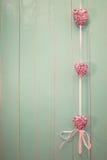 Os corações brilhantes cor-de-rosa no vintage esverdeiam o fundo de madeira Fotografia de Stock Royalty Free