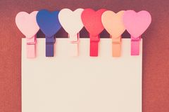 Os corações coloridos pequenos guardam uma nota de papel em um fundo marrom Imagem de Stock