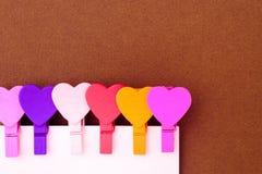 Os corações coloridos pequenos guardam uma nota de papel O conceito de uma nota a Fotos de Stock Royalty Free
