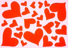 Os corações dão forma ao corte de papel cor-de-rosa no fundo vermelho imagens de stock