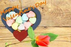 Os corações de madeira com doces Valentine Background com rosa do vermelho e o Valentim feliz text no fundo de madeira velho Imagem de Stock