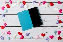 Os corações dispersaram em uma tabela de madeira e em um smartphone Imagens de Stock Royalty Free