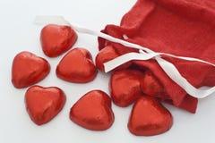 Os corações do chocolate saem de uma meia do Natal Imagens de Stock Royalty Free