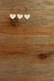 Os corações do Valentim branco do amor que penduram no backgrou de madeira da textura Imagem de Stock Royalty Free