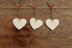 Os corações do Valentim branco do amor que penduram no backgrou de madeira da textura Imagens de Stock Royalty Free