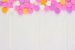 Os corações dos doces do dia de Valentim cobrem a beira sobre a madeira branca Imagens de Stock