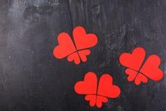 Os corações são alinhados nas borboletas em um fundo de pedra Imagens de Stock