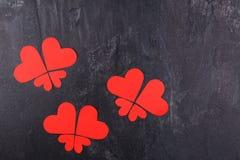 Os corações são alinhados nas borboletas em um fundo de pedra Vista de acima Imagens de Stock