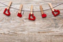 Os corações vermelhos com pregadores de roupa em uma trela penduraram na frente do fundo de madeira rústico com espaço do texto c Imagem de Stock
