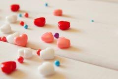 Os corações vermelhos, cor-de-rosa e brancos dão forma a doces na tabela de madeira Fotos de Stock Royalty Free