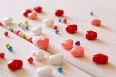 Os corações vermelhos, cor-de-rosa e brancos dão forma a doces na tabela de madeira Imagem de Stock Royalty Free