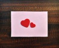 Os corações vermelhos do Valentim forram o cartão do presente na tabela Fotografia de Stock