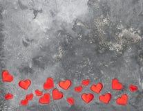 Os corações vermelhos são dispersados em um fundo textured cinzento Disposição lisa Copie o espaço fotografia de stock