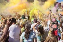 Os corredores criam a explosão da cor com os pacotes coloridos do amido de milho Fotografia de Stock Royalty Free