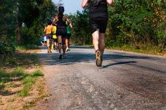 Os corredores da fuga correm sua corrida com roupa suado no pavem foto de stock royalty free