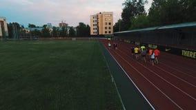 Os corredores da opinião do zangão agrupam movimentar-se na trilha do estádio do esporte na noite filme