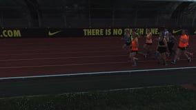 Os corredores da vista aérea agrupam movimentar-se na trilha do estádio do esporte na noite filme