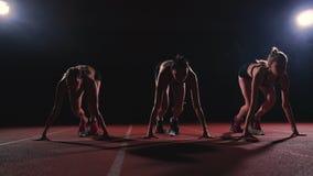 Os corredores fêmeas no atletismo seguem o agachamento nos blocos começar antes de uma raça no movimento lento filme