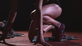 Os corredores fêmeas no atletismo seguem o agachamento nos blocos começar antes de uma raça no movimento lento vídeos de arquivo