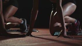 Os corredores fêmeas no atletismo seguem o agachamento nos blocos começar antes de uma raça no movimento lento video estoque