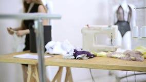 Os cortes da costureira rosqueiam da tela do laço em máquinas de costura na oficina video estoque