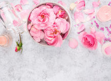 Os cosméticos cor-de-rosa das rosas ajustaram-se com creme, garrafa, velas, pétalas e sal do mar Fotografia de Stock Royalty Free